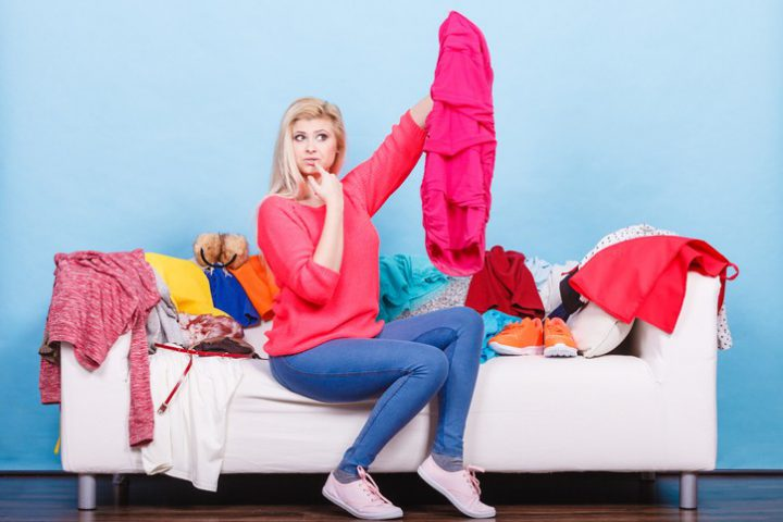 Woman does not know what to wear sitting on messy couch with piles of clothes and looking through clothing.
